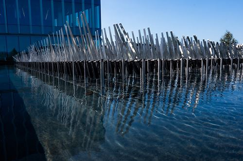 moving metal blades over a pool of water, designed to look like grass blowing in the wind.